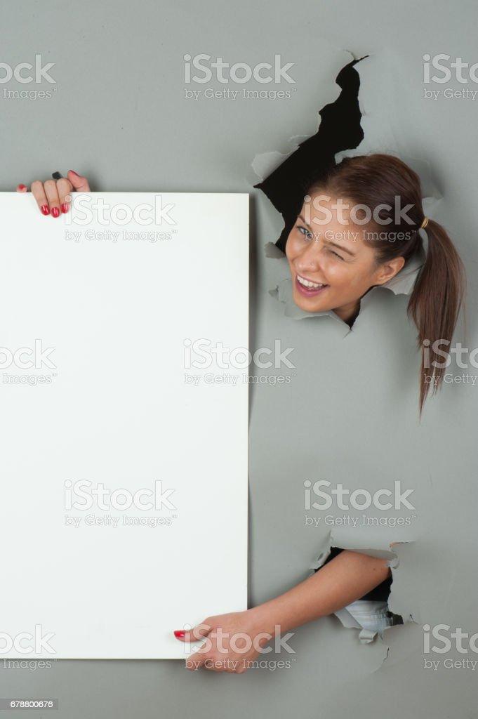 Woman looking through torn paper photo libre de droits
