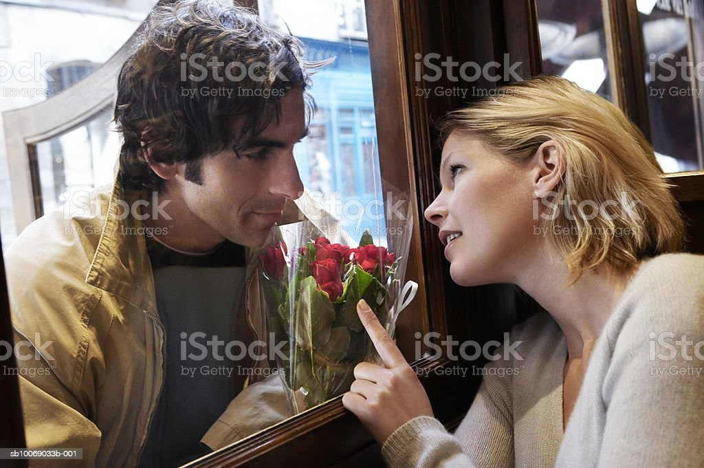 Woman looking through window at man holding flowers royalty-free stock photo