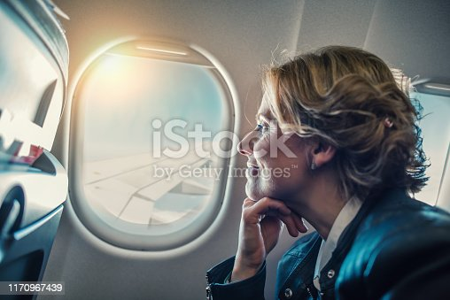Close-up of passenger looking out through window on a plane