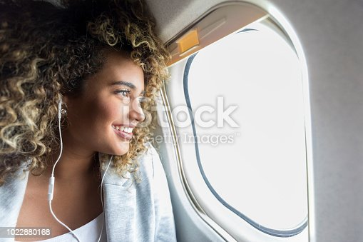 Confident young mixed race woman smiles while looking through window on aircraft. She is wearing earbuds.