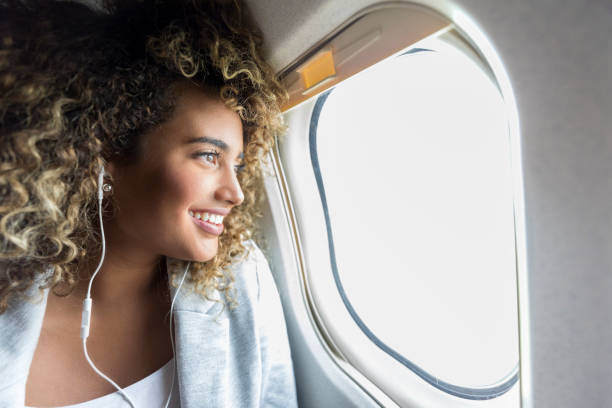 Woman looking through window on airplane Confident young mixed race woman smiles while looking through window on aircraft. She is wearing earbuds. aboard stock pictures, royalty-free photos & images