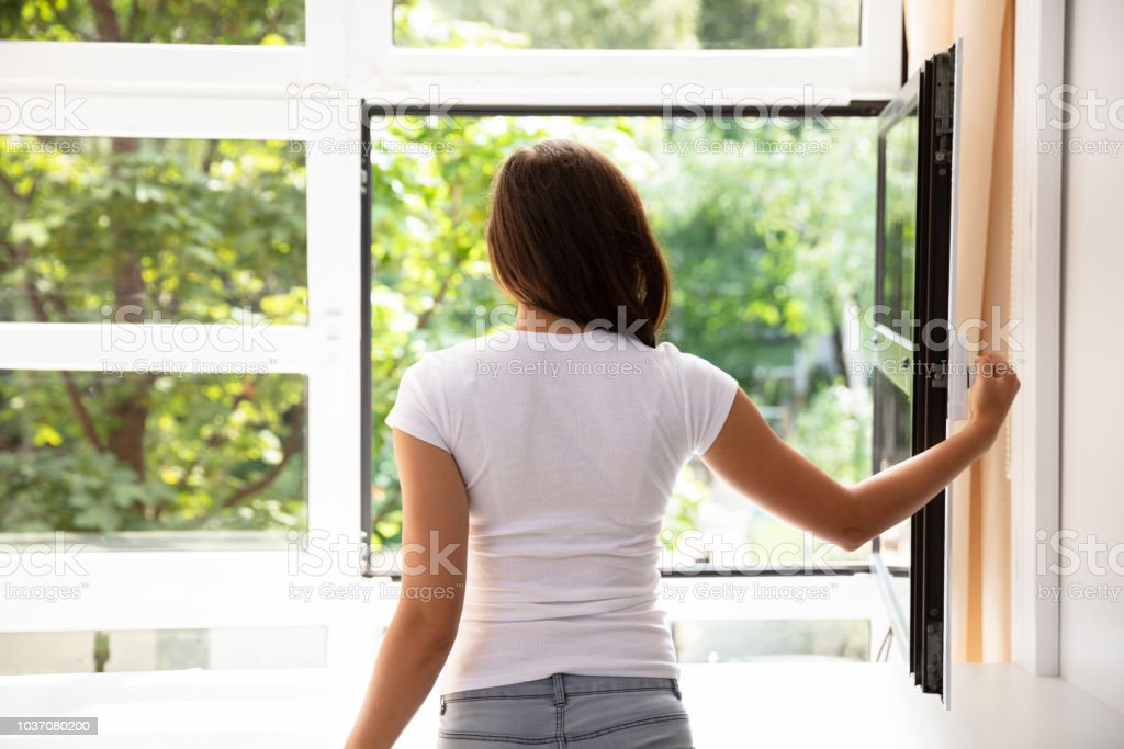 Side View Of A Woman Looking Through Window At Home