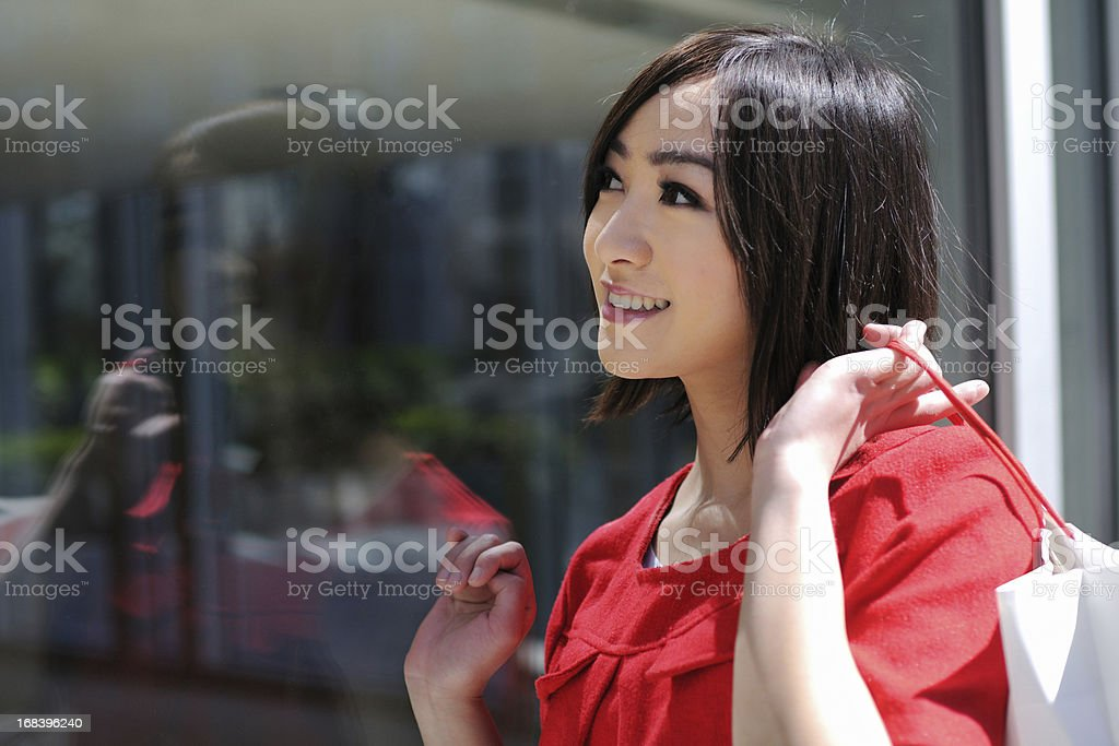 A beautiful asian woman is looking through window