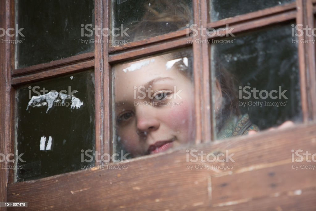 Curious young woman looks outside through the glass on an old wooden...