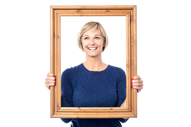 Woman looking through wooden frame stock photo