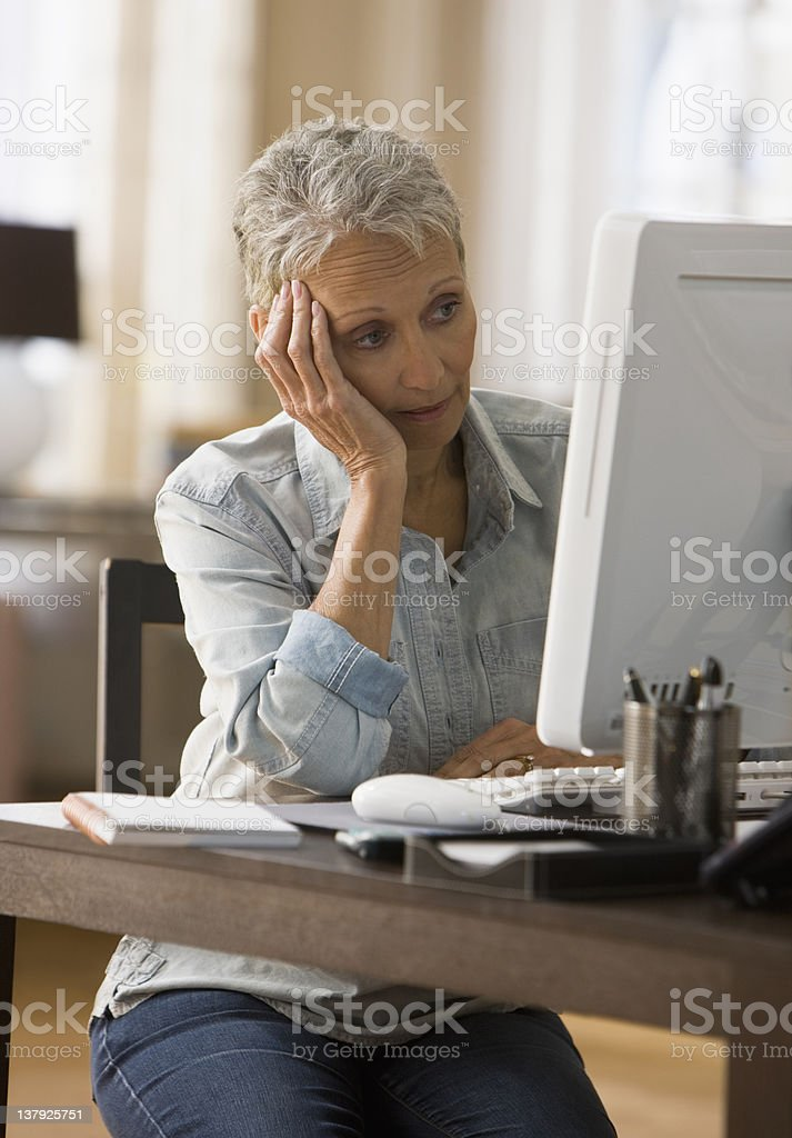 Woman looking tired in front of her computer stock photo
