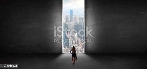 Woman standing in a dark room and looking outside to a cityscape view