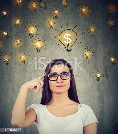 Portrait of a thinking young woman looking up at dollar idea light bulbs above head deciding how to earn morney isolated on gray wall background