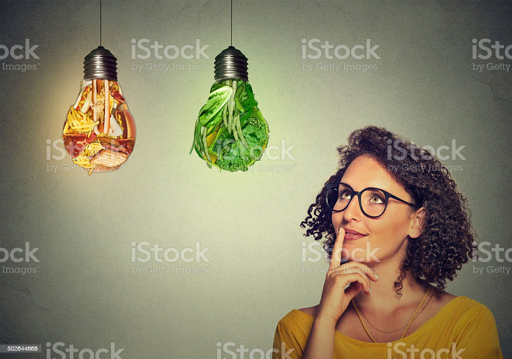 woman looking up at junk food vegetables light bulb stock photo