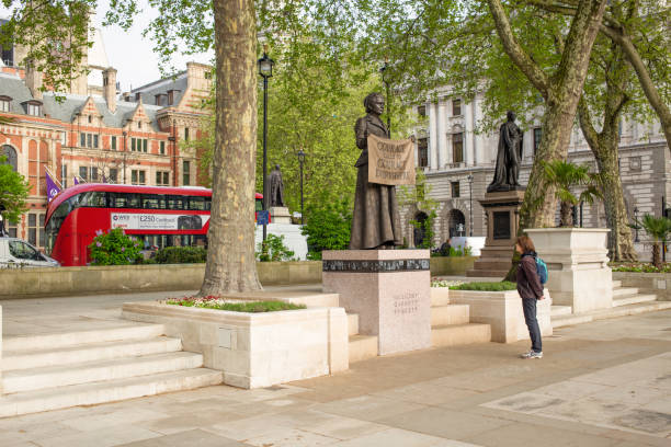 Woman looking up at the newly erected statue of Millicent Fawcett in Parliament Square, London, UK, London, England 4th May, 2018 - Woman looking up at the newly erected statue of Millicent Fawcett in Parliament Square, London, UK, She campaigned for women's right to vote during the early 20th Century and is seen as one of the most influential feminists of the past 100 years. suffragist stock pictures, royalty-free photos & images
