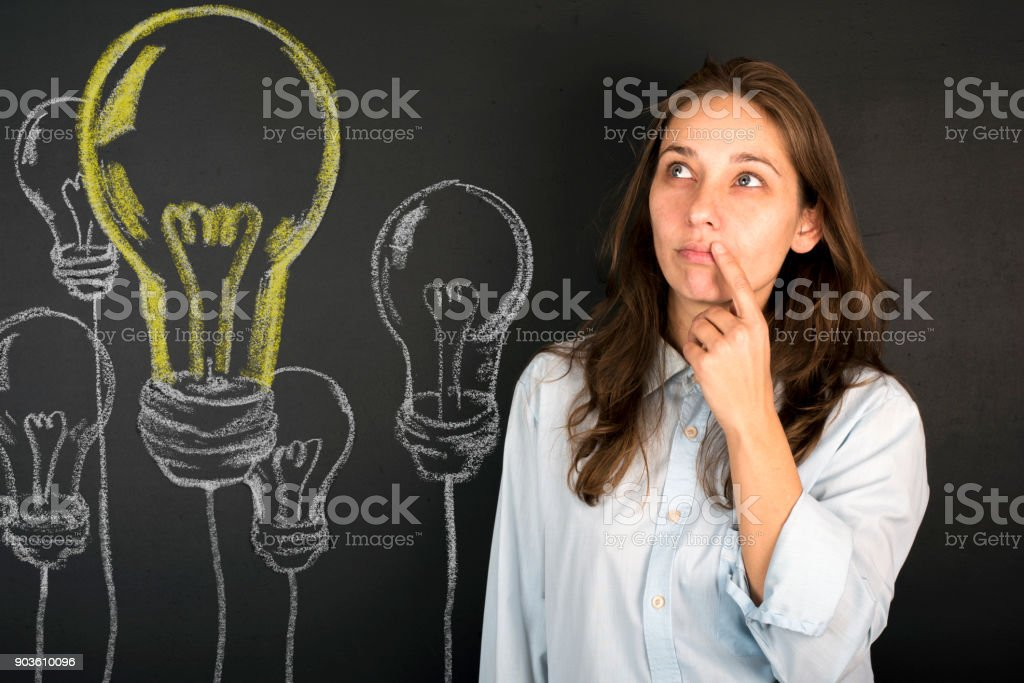 Woman looking up with light idea bulb stock photo