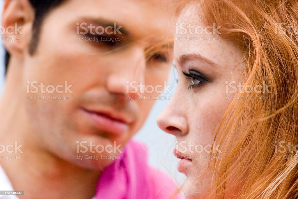 A woman looking upset as a man looks at her royalty-free stock photo
