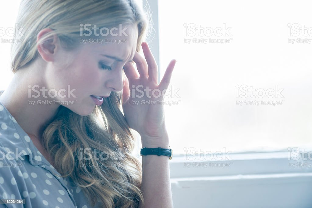 Woman looking upset or in pain. stock photo
