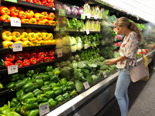 Woman looking vegetables Cheerful woman selecting fresh vegetables (broccoli) in a supermarket. Horizontal composition. Side view. Indoors. produce aisle stock pictures, royalty-free photos & images