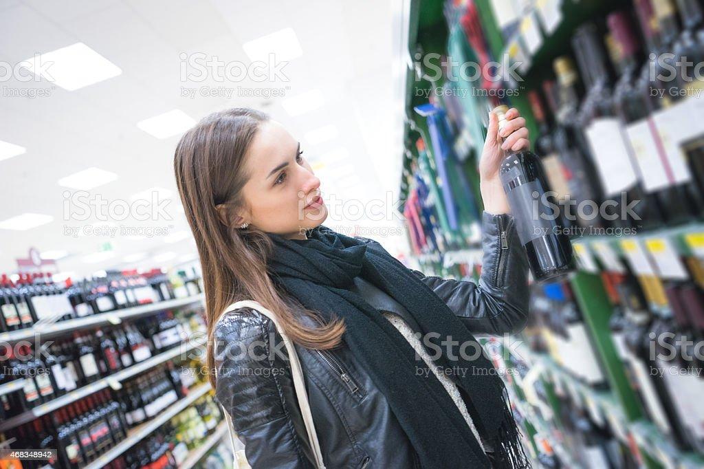 Woman Looking Wine Bottles stock photo