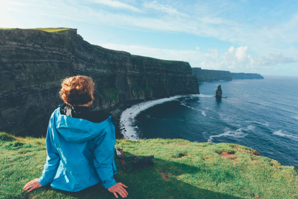 Woman looks at Cliffs of Moher in Ireland