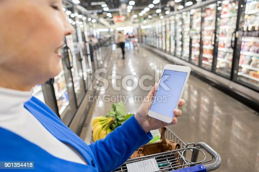 istock Woman looks at grocery list on smart phone 901354418