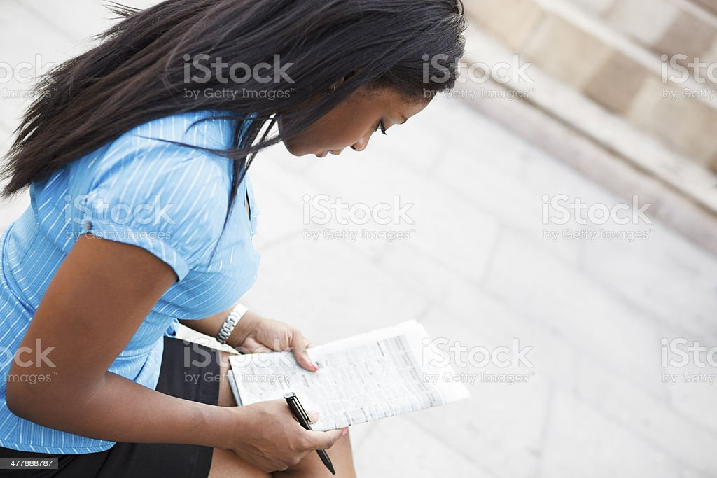 Woman Looks at Newspaper Listings Outdooors royalty-free stock photo