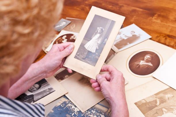 vrouw kijkt naar oude foto's van familieleden - senior fotoboek stockfoto's en -beelden