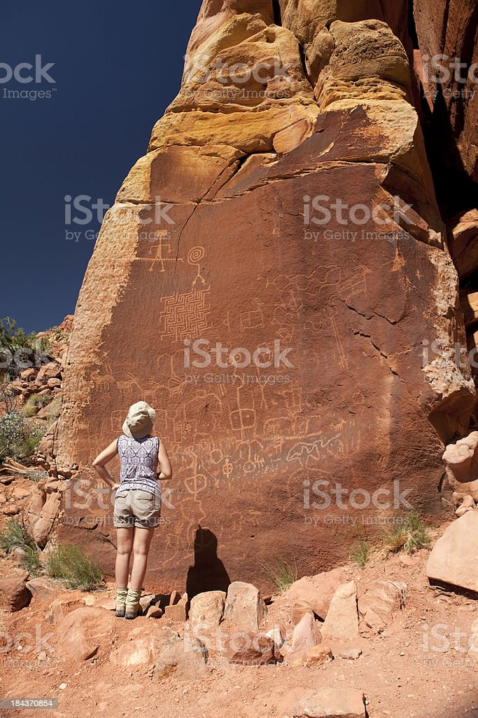 Woman looks at petroglyphs Vermilion Cliffs National Monument Arizona royalty-free stock photo