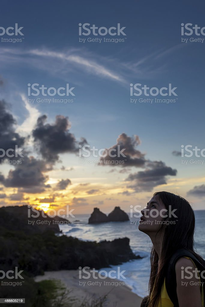 Woman looks at sunset in Fernando de Noronha ,Brazil stock photo
