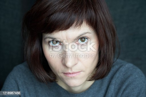 Woman looks from under her brows, frowning and stern. A serious face close up. Anger and wariness. Beautiful caucasian female with dark hair at home during quarantine