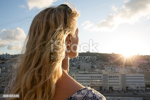 Woman looks out across city scene at sunrise, close up