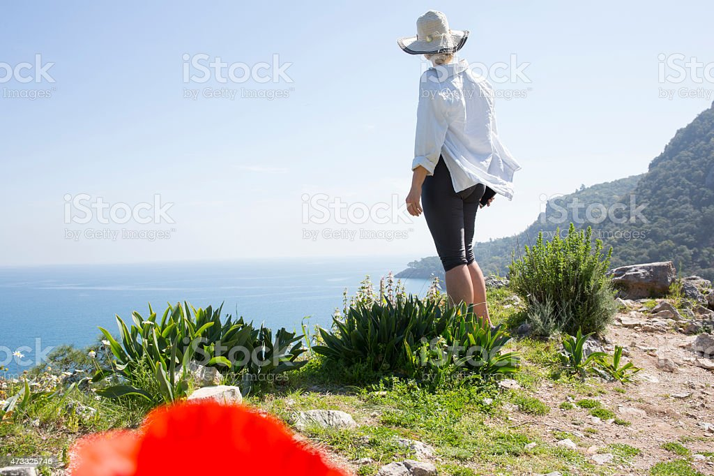 Woman looks out across sea from mountain ridge crest stock photo