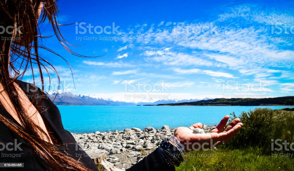 Woman looks out across turquoise lake towards Mount Cook small crystal rests in her hand stock photo