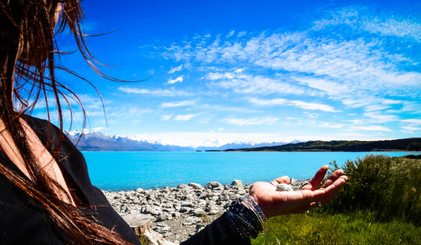 Woman looks out across turquoise lake towards Mount Cook small crystal rests in her hand Edge side view of a beautiful woman standing on a rocky beach, looking out across a turquoise lake towards Mount Cook, a small pebble like crystal rests in her open hand. crystal healing stock pictures, royalty-free photos & images