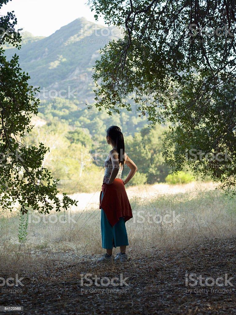 Donna si affaccia su montains e alberi foto stock royalty-free