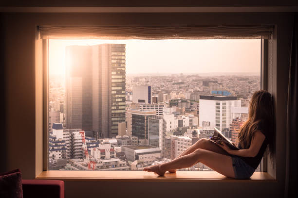 Woman looks out of her hotel window in Shibuya, Tokyo, Japan stock photo