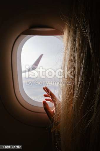 900763322 istock photo Woman looks out the window of an airplane. Hand near the porthole. Girl on the plane. Airplane wing, scenic view. Beautiful cloud, blue sky. Traveling by plane, adventure. Air transport. Aviation 1189175752