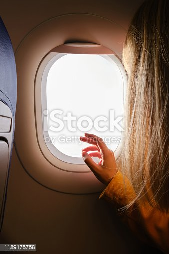 900763322 istock photo Woman looks out the window of an airplane. Hand near the porthole. Girl on the plane. Airplane wing, scenic view. Beautiful cloud, blue sky. Traveling by plane, adventure. Air transport. Aviation 1189175756