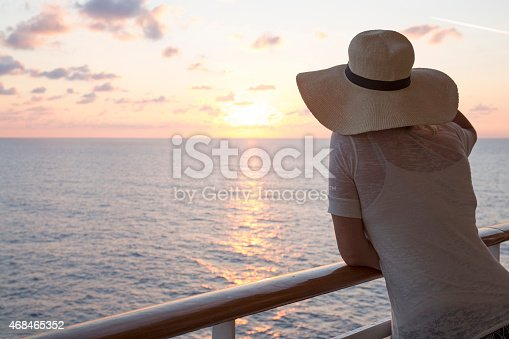 Woman looks out to sea from railing of ship, sunrise
