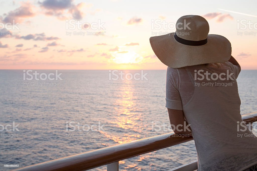 Woman looks out to sea from railing of ship stock photo