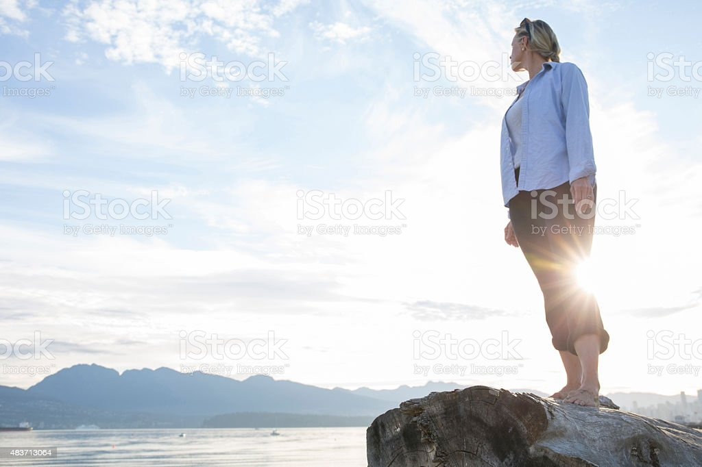 Woman looks over her shoulder towards mountains stock photo