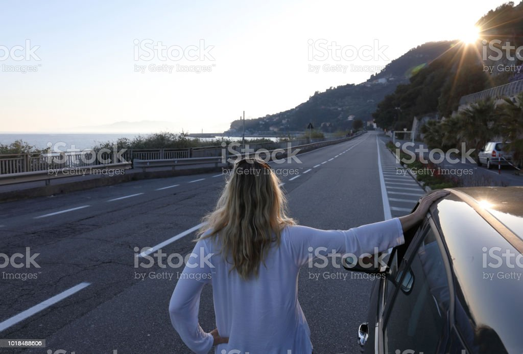 Woman looks over road from car to sea. Sunshine over hills in Italy