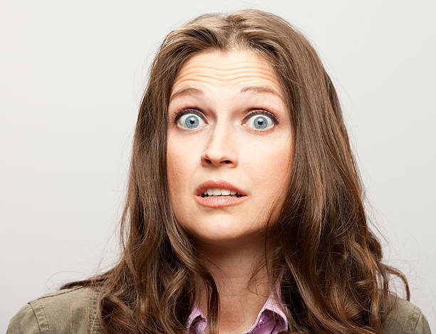 Woman Looks Scared Pretty woman with huge eyes looks scared or amazed. raised eyebrows stock pictures, royalty-free photos & images