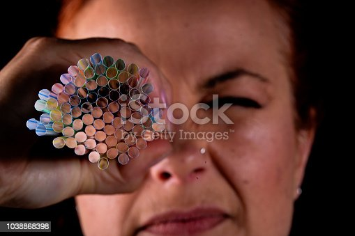Woman looks through plastic straws