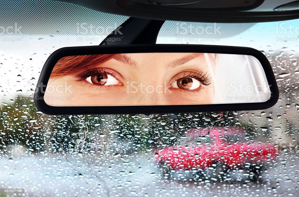 woman looks to rear-view mirror stock photo