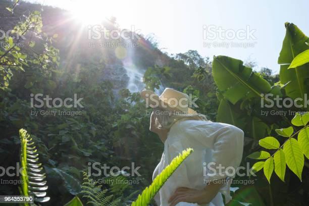 Foto de Mulher Olha Para A Cachoeira Na Floresta Tropical Ao Nascer Do Sol e mais fotos de stock de 55-59 anos