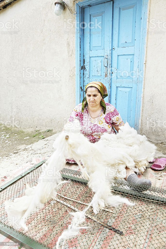 Woman loosening wool with stick royalty-free stock photo