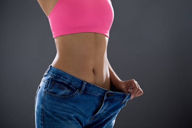 woman loses weight Slim woman in  jeans is showing how much weight she lost dieting stock pictures, royalty-free photos & images