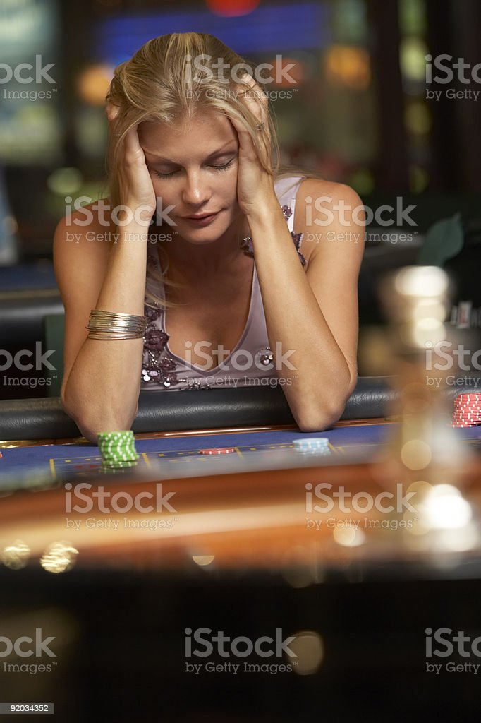 Woman losing at roulette table stock photo