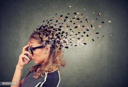 istock Woman losing parts of head as symbol of decreased mind function. 920001120