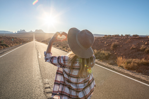 Woman loves USA, makes heart shape finger frame; Rear view of woman standing on long highway road leading to Monument Valley in USA. People travel America concept