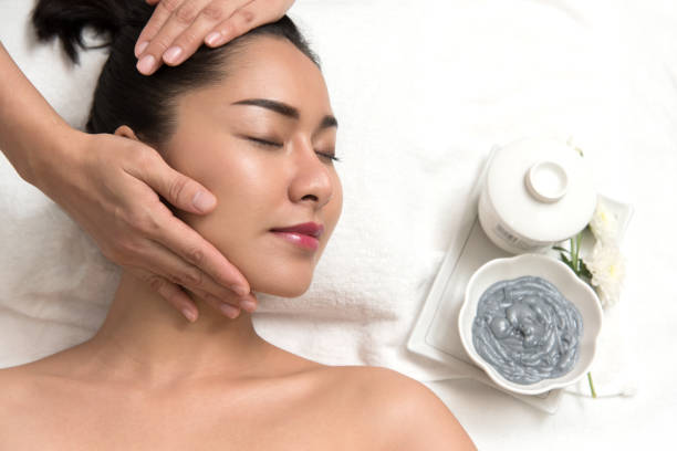 woman lying and preparation face or head massage in spa - thai massage stock photos and pictures