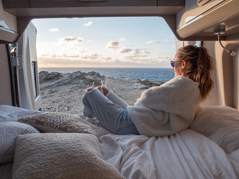 Road trip concept, woman living the van life experience watching stunning view while lying on the bed of the back of her camper