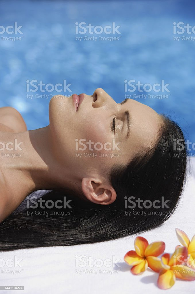 Woman lying by pool, eyes close royalty-free stock photo